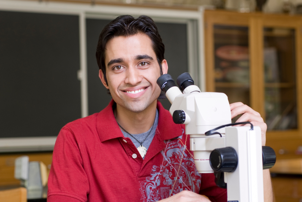 Student sits behind microscope smiling