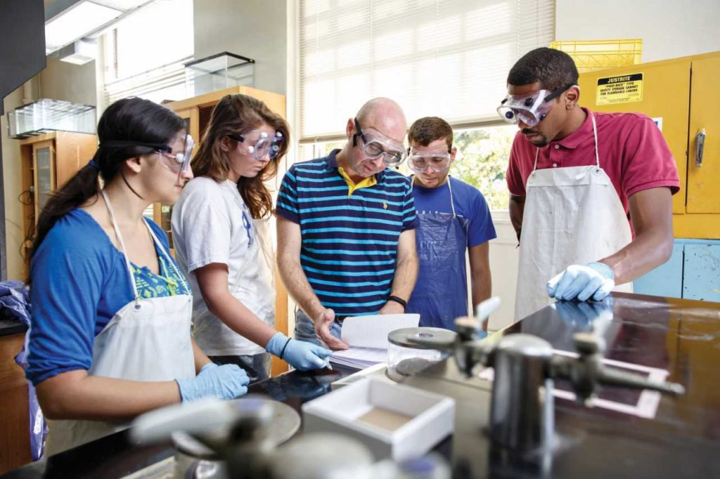 Students In Laboratory Gathering around Professor